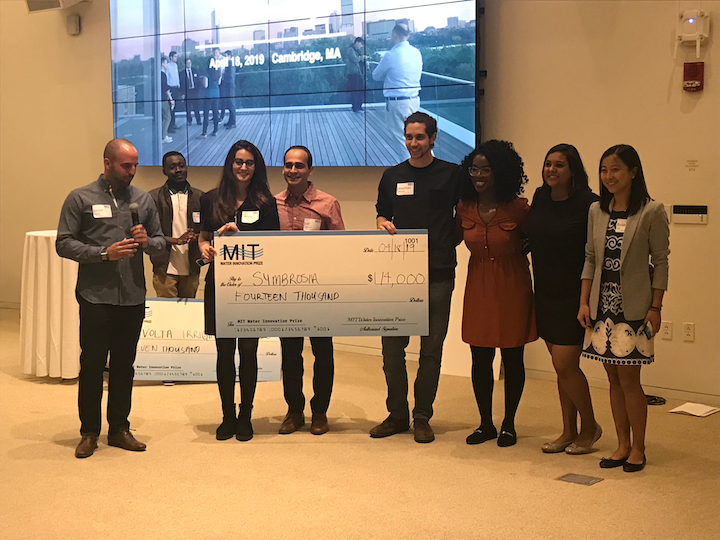 MIT MBA student Javier Renna (left) presents the MIT Water Prize winners with their award.
