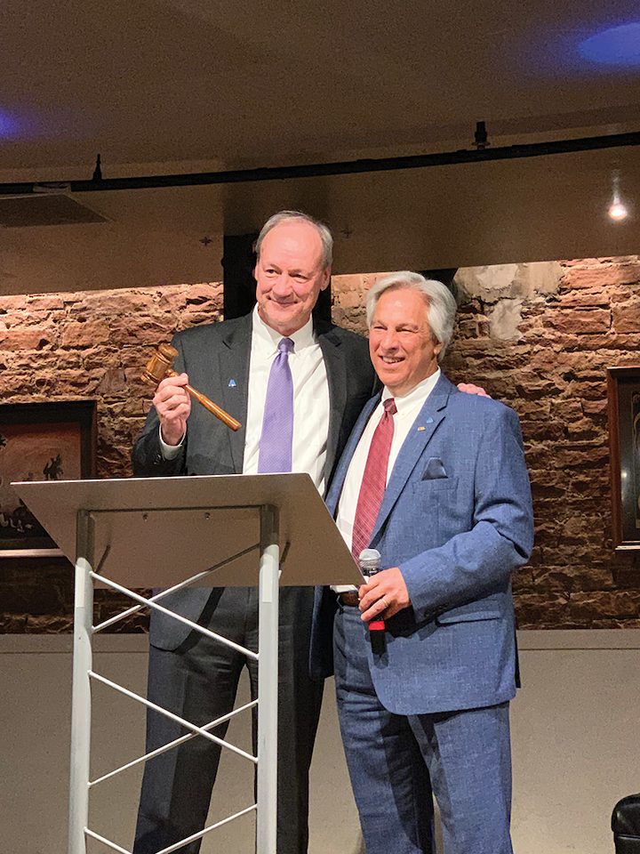 Jim Williams (left) accepts the gavel from David Rager during AWWA's ACE 2019 conference in Denver. Photo courtesy SUEZ N.A.